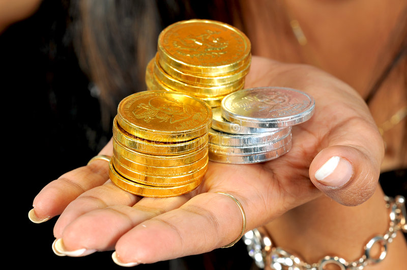 Gold and silver coins. On lady's hand stock photo