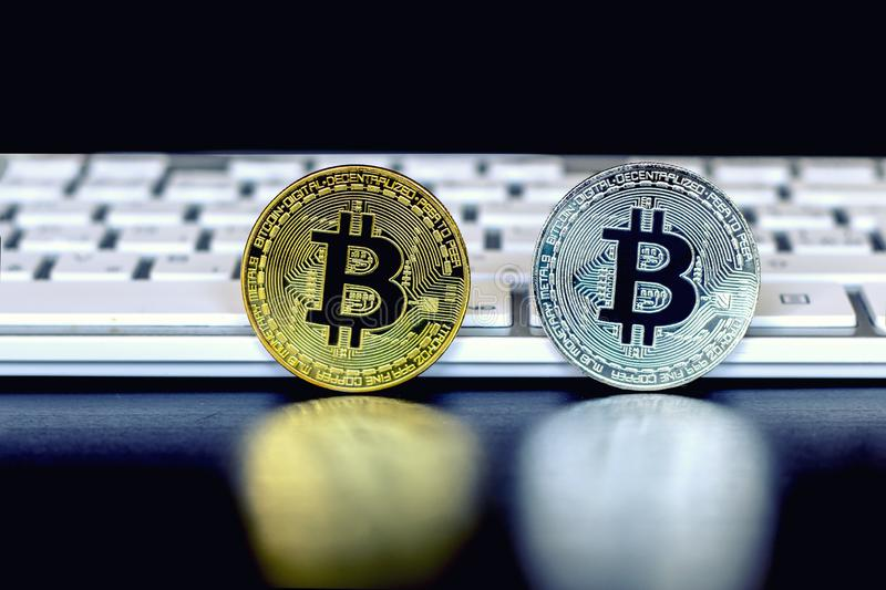 The gold and silver coins of the bitcoin stands on the black background in front of the white keyboards stock photo