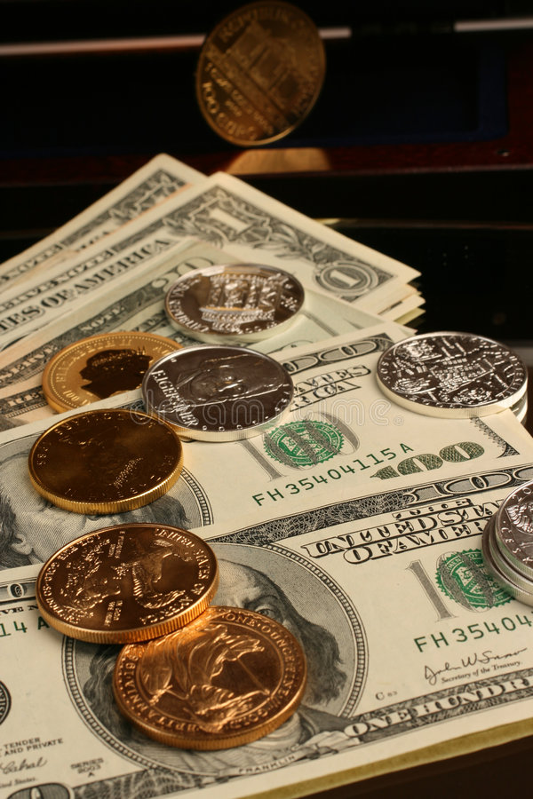 Gold and silver coins and paper money stock photography