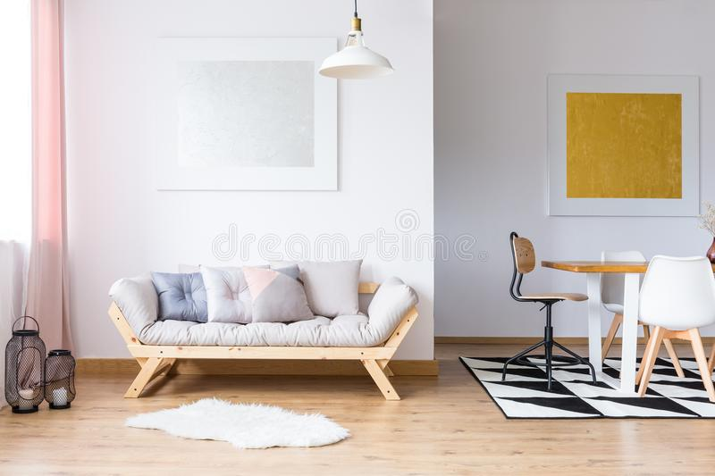 Gold and silver gallery room. Gold and silver gallery in spacious room with pastel pillows on sofa and dining table on black and white carpet royalty free stock image