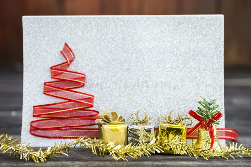 Gold and silver gift box with Christmas decoration over blurred silver glitter paper background royalty free stock photo