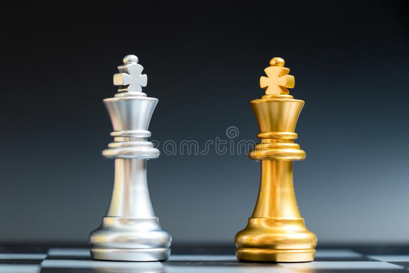 Gold and silver king chess piece face in chessboard. On black background royalty free stock image
