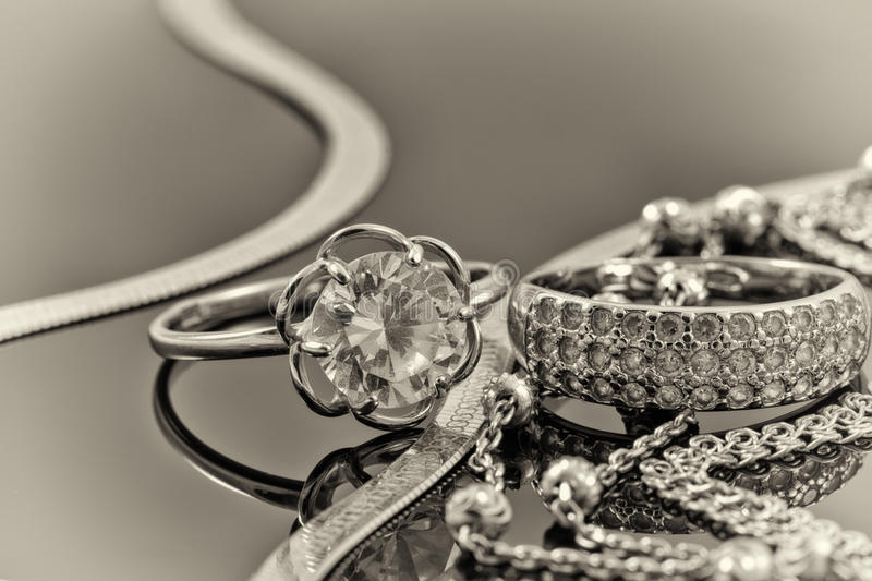 Gold, silver rings and chains. Of different styles are lying together on the reflecting surface royalty free stock photo