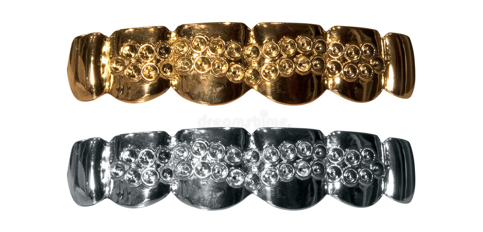 Gold and silver teeth. Shiny gold and silver isolated fake teeth royalty free stock photos