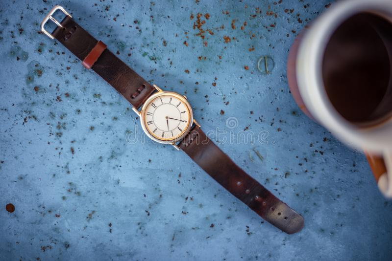 Gold/silver vintage wrist watch with brown leather bracelet. Gold/silver vintage wrist watch with brown leather bracelet on rustic blue metal bench suggesting royalty free stock image