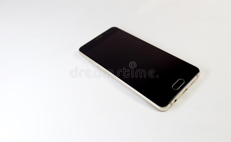 Gold smartphone  on a white background. Premium smartphone shining in its gold and metal body stock image