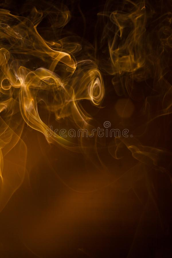 Gold smoke on black background stock images