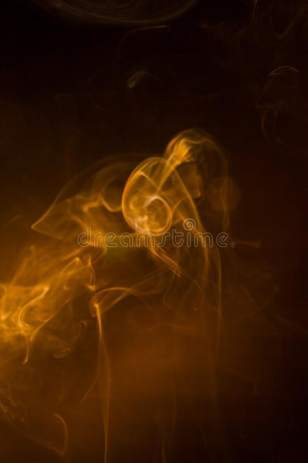 Gold smoke on black background royalty free stock image