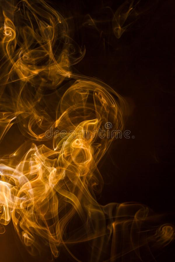 Gold smoke on black background royalty free stock images