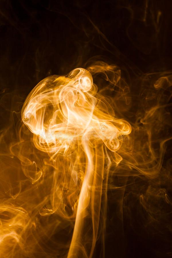 Gold smoke on black background stock photo