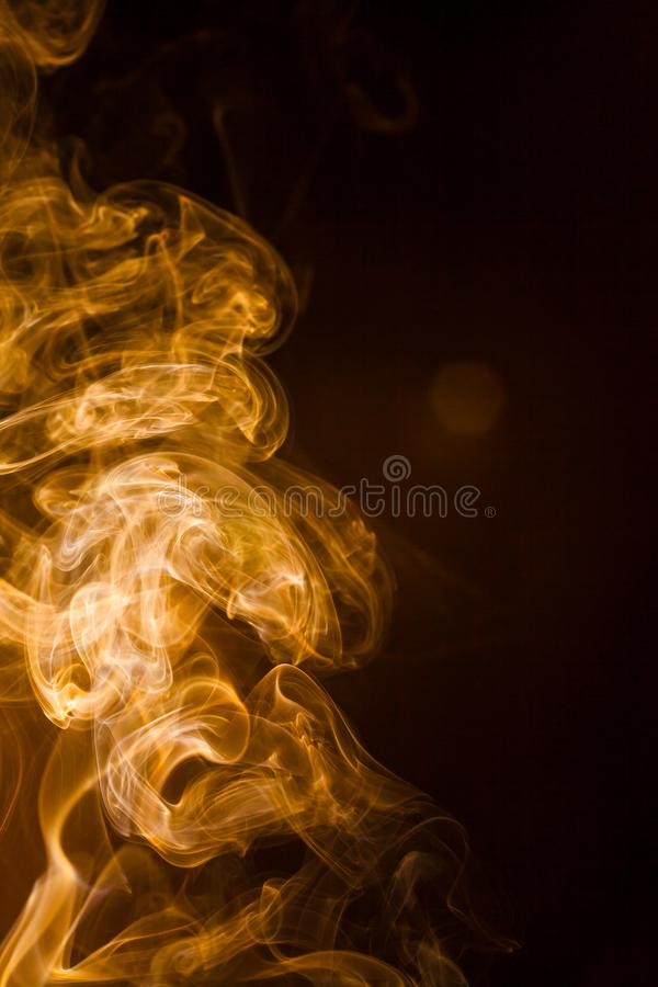 Gold smoke on black background. Abstract, air, aroma, art, burning, cigarette, color, concept, creativeness, curve, delicate, design, detail, dynamic, effect royalty free stock photo