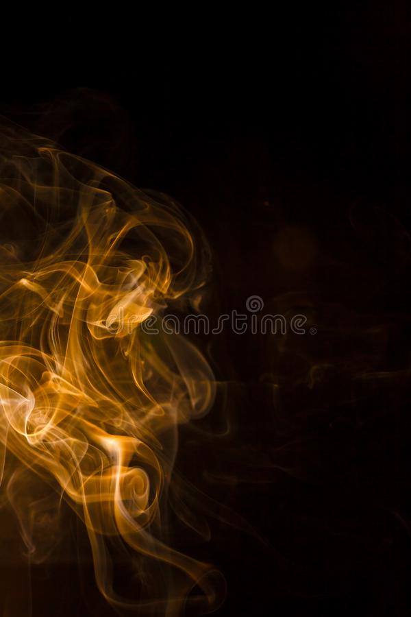 Gold smoke on black background. Abstract, air, aroma, art, burning, cigarette, color, concept, creativeness, curve, delicate, design, detail, dynamic, effect royalty free stock photography
