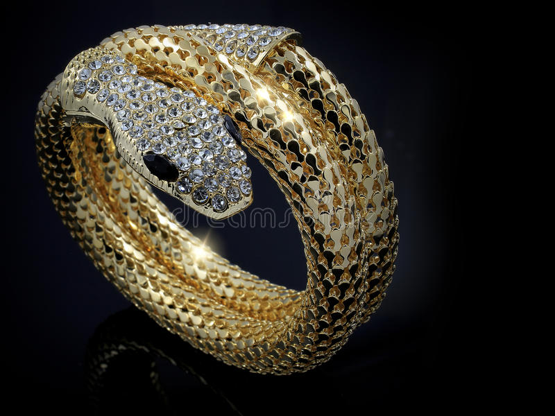 Gold snake bracelet for women. Black background royalty free stock images
