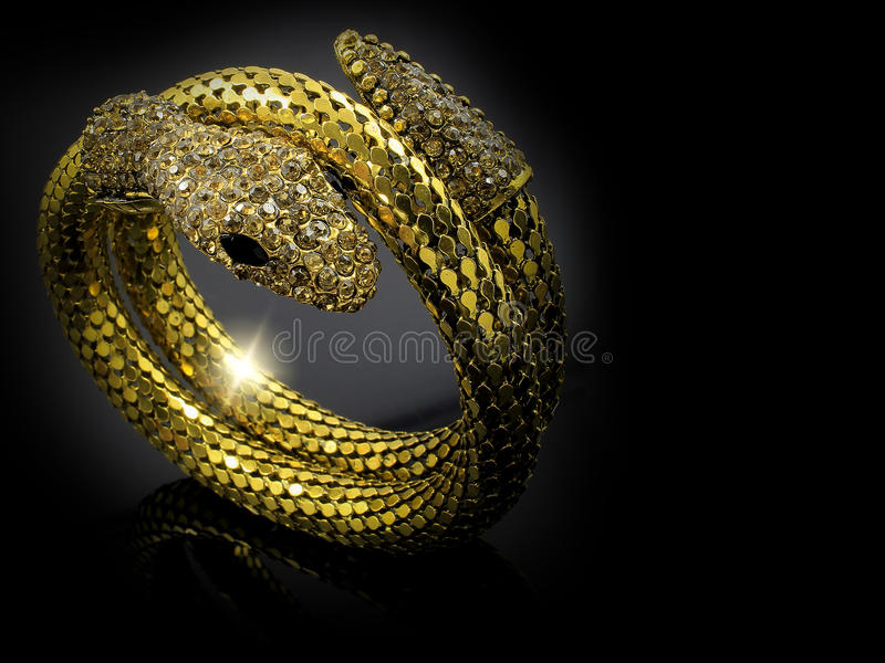 Gold snake bracelet for women. Black background stock photography