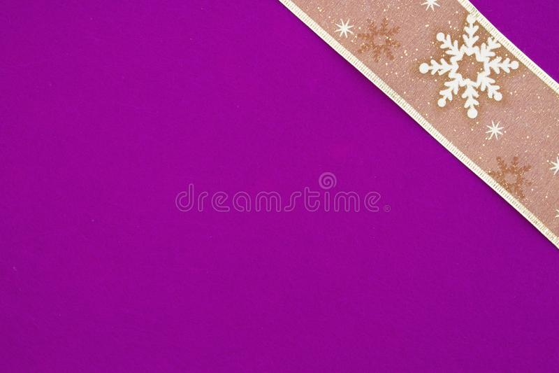 Gold snowflake ribbon on bright purple textured felt material background royalty free stock photos