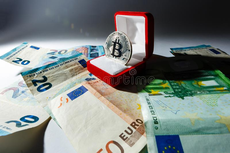 Gold souvenir coin bitcoin lies in the gift box for jewelry on the background of dollars royalty free stock photography