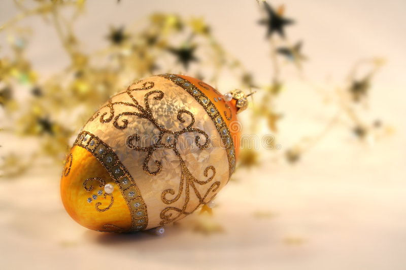 Gold and sparkling. Gold Christmas ball with small stars on a pale white background stock images