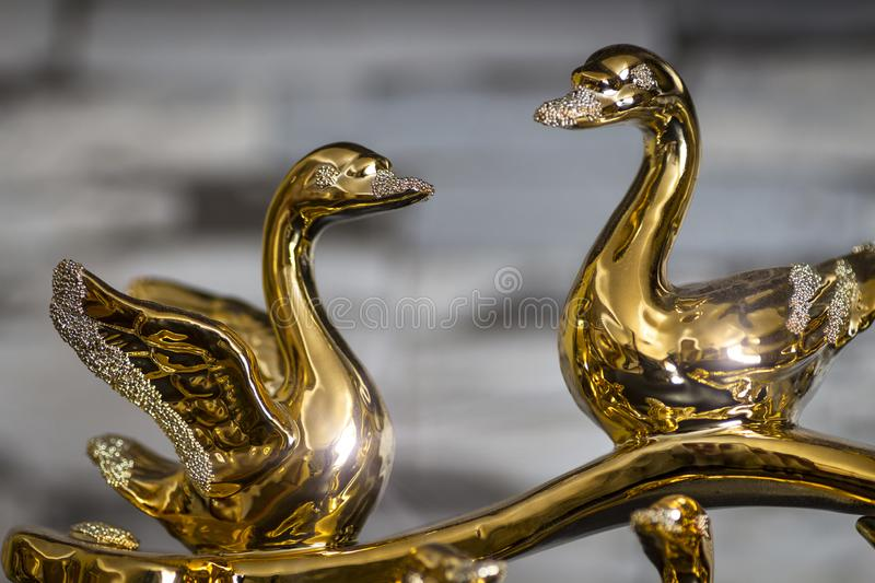 Gold statuette of swans. Gold statuette of two enamored swans close-up royalty free stock images