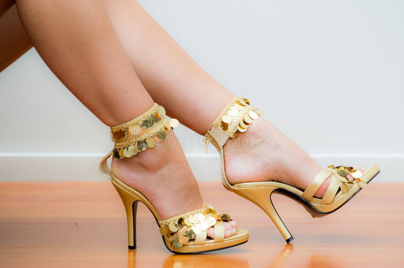 Gold Stiletto Shoes. Models legs showing a Pair of Ladies gold stiletto high heel shoes with sequins royalty free stock photo