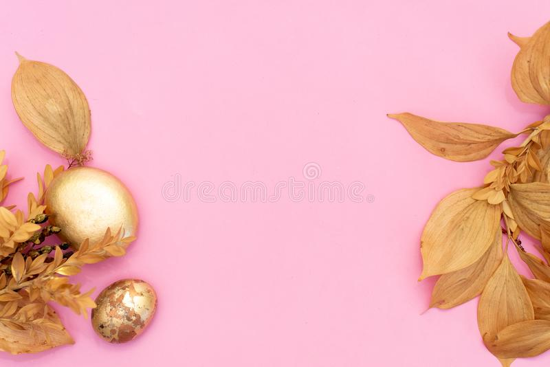 Gold stones and dried flowers on a pink background. Spa background and gold leaf royalty free stock photo