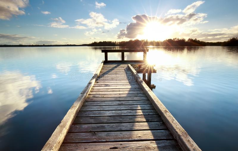 Gold sunshine over wooden pier on big lake royalty free stock images