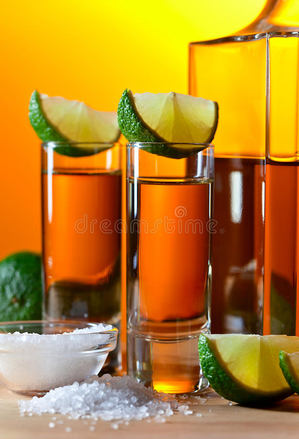 Gold tequila with salt and lime. On wooden table stock image