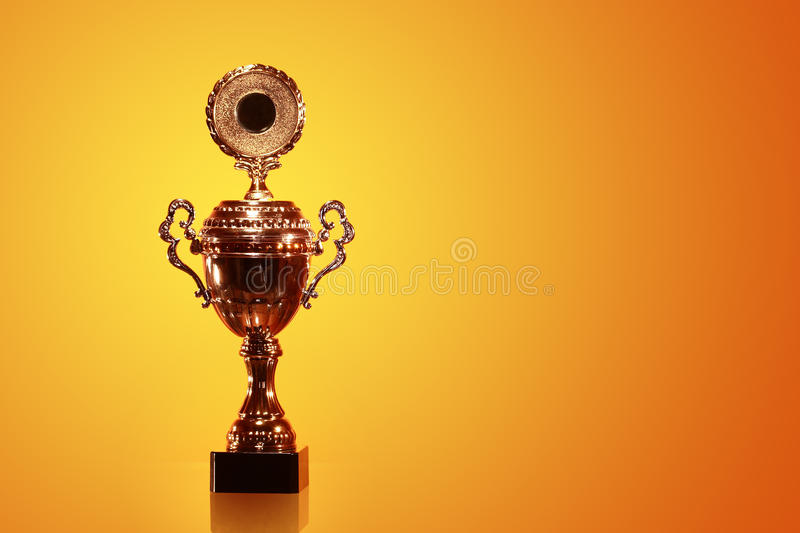 Gold Trophy. High gold trophy on orange background with free space for text stock photography