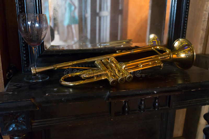 Gold trumpet laying on a table with a glass of wine and young lady reflection in the mirror. Gold trumpet laying on a table with a glass of wine and a young lady royalty free stock photo