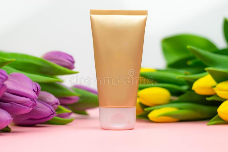 Empty tube of cream on a pink background with flowers royalty free stock photo