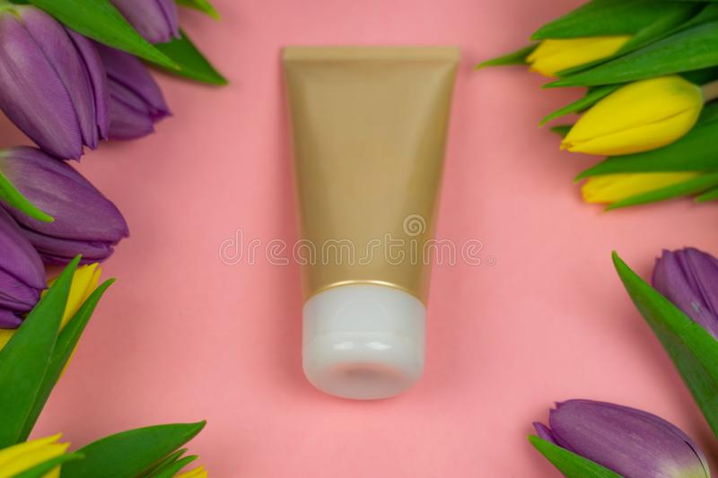 Empty tube of cream on a pink background with flowers stock photography