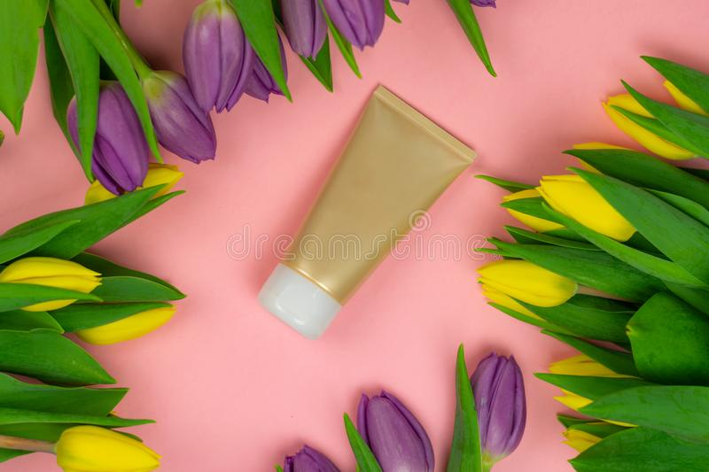 Empty tube of cream on a pink background with flowers royalty free stock image