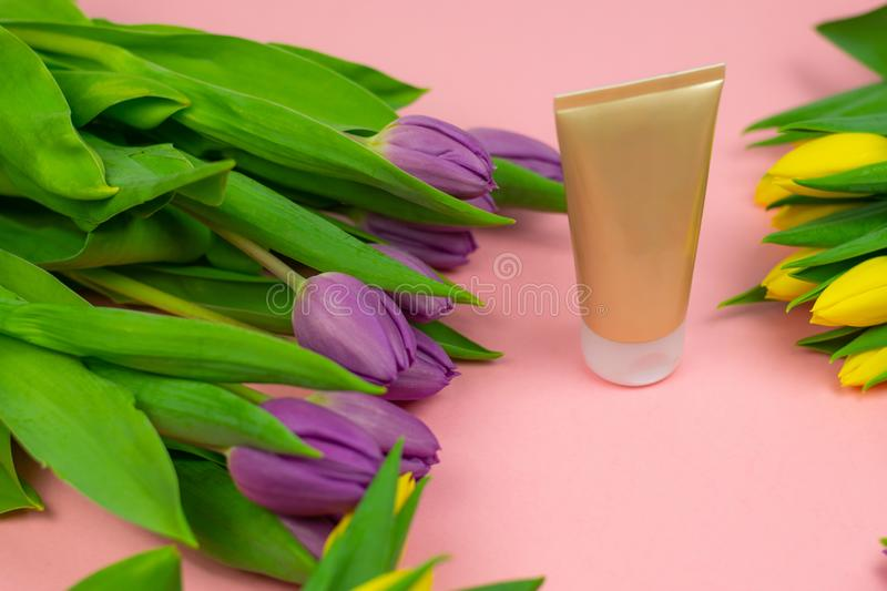 Empty tube of cream on a pink background with flowers royalty free stock photography