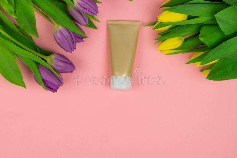Empty tube of cream on a pink background with flowers stock image