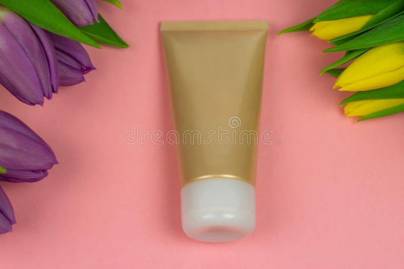 Empty tube of cream on a pink background with flowers royalty free stock images
