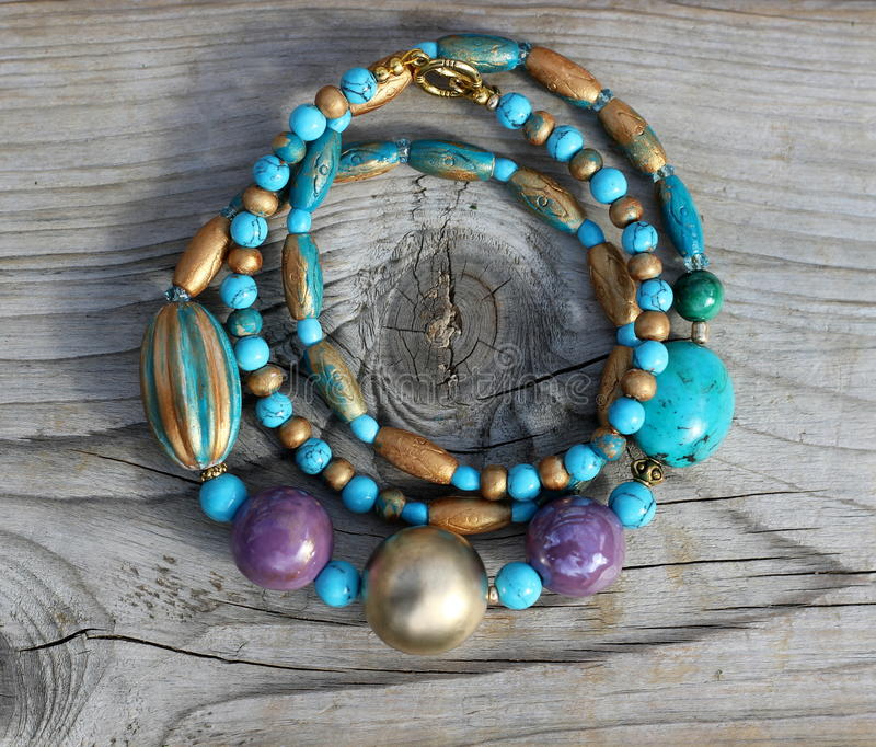 Gold and turquoise necklace. Handmade turquoise and ceramic modern style necklace jewellery. Golden romantic boho necklace on wooden backdround royalty free stock image