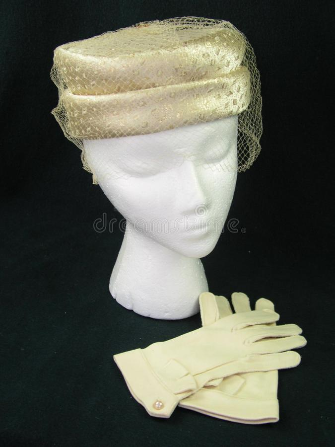 Gold Veiled Pillbox Hat and Gloves on a Woman Mannequin royalty free stock images