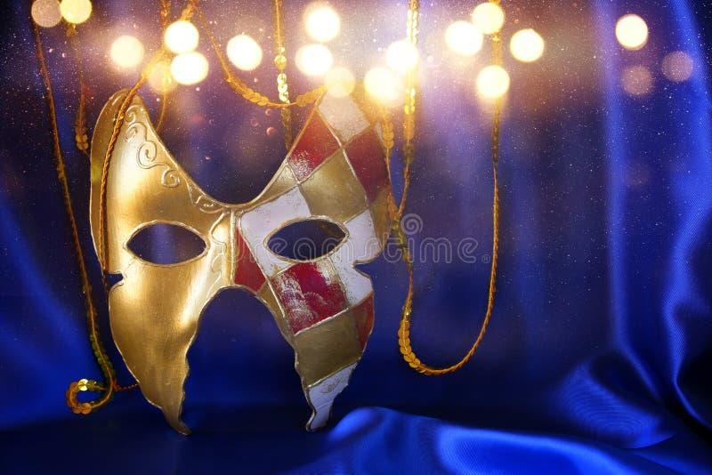 Gold venetian mask on blue silk background. Image of elegant gold venetian mask on blue silk background stock photography