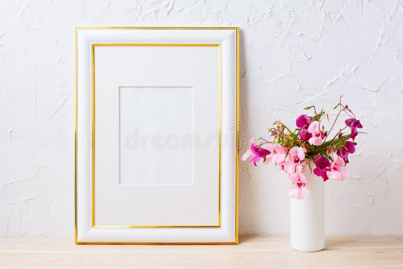 Gold verzierte Rahmenmodell mit rosa und purpurrotem Blumenblumenstrauß stockfotos