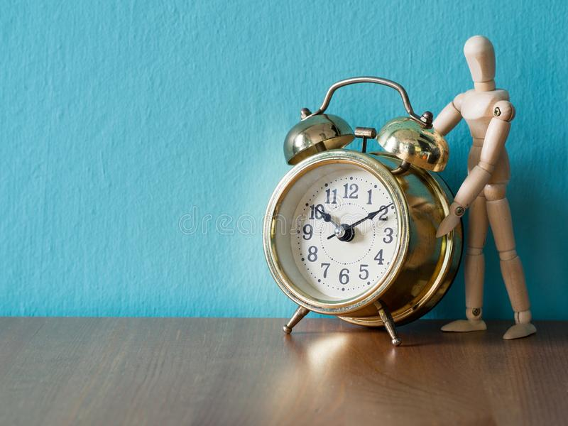 Gold vintage alarm clock on the wood table in the font of wooden puppet stand. the background is blue and copy space for text. And content stock image