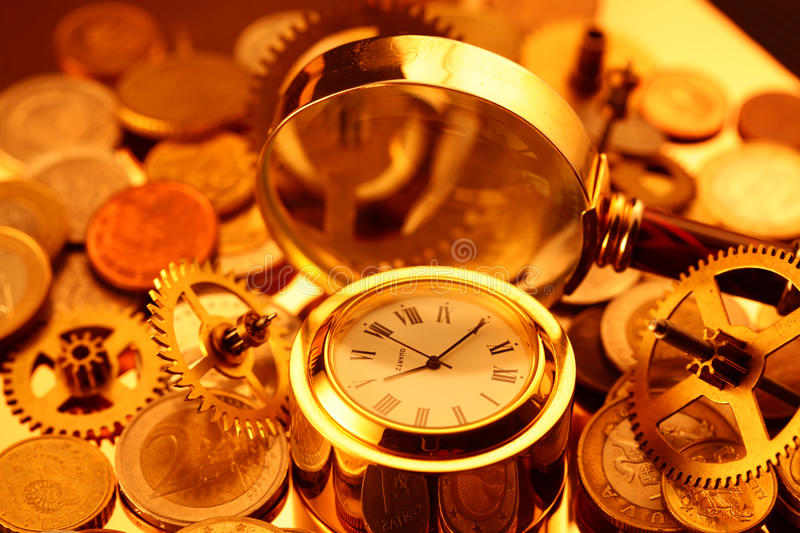 Gold watches, coins, gears and magnifying glass stock photo
