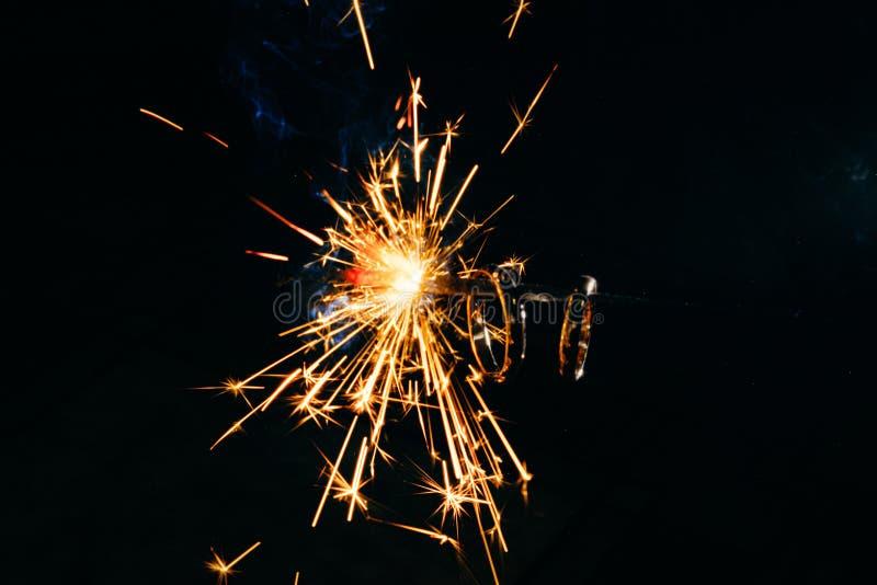 gold wedding engagement ring on burning bengal light. orange sparks on black dark background. Marriage, wedding for christmas royalty free stock images