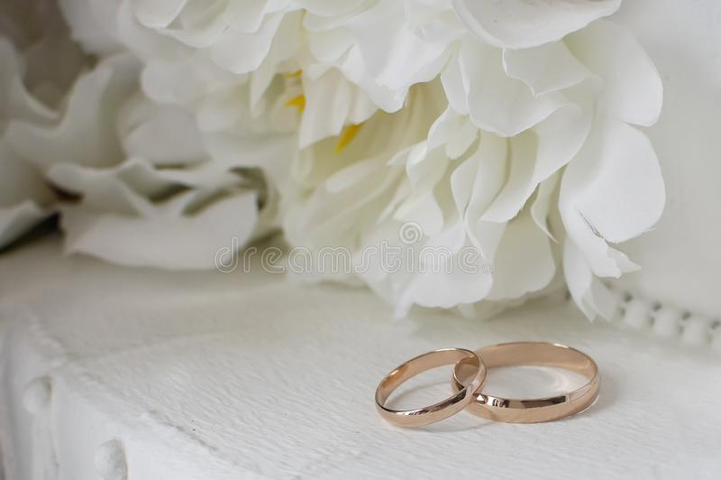 Gold wedding rings on a background of white decorative flowers royalty free stock images