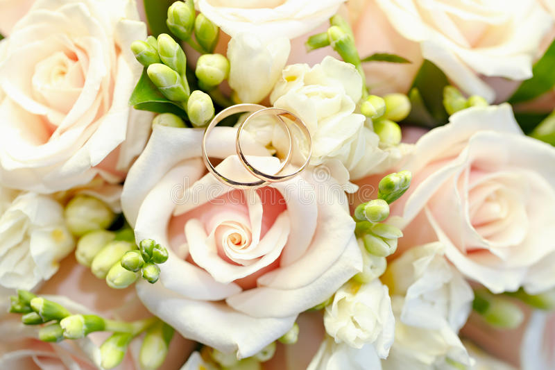 Gold wedding rings on bouquet of flowers for the bride. Gold wedding rings on a bouquet of flowers for the bride royalty free stock images