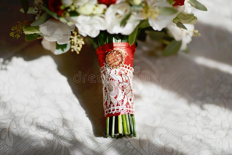 Gold wedding rings on a bouquet of flowers with white lace and a red ribbon and brooch royalty free stock image