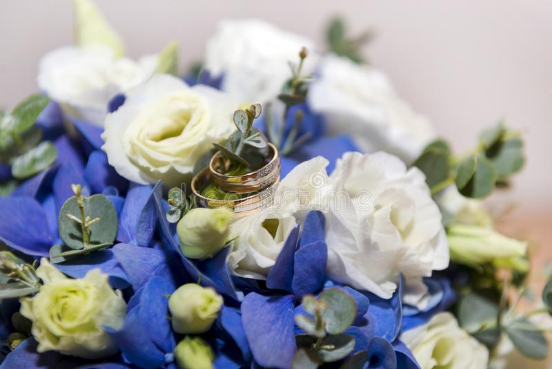 Gold Wedding Rings On A Bouquet Of White And Blue Flowers Stock ...