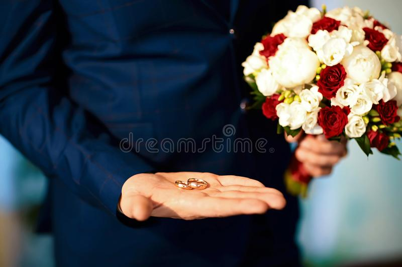 Gold wedding rings in the bride`s hand in a suit with a bouquet of flowers of white and red color.  royalty free stock image