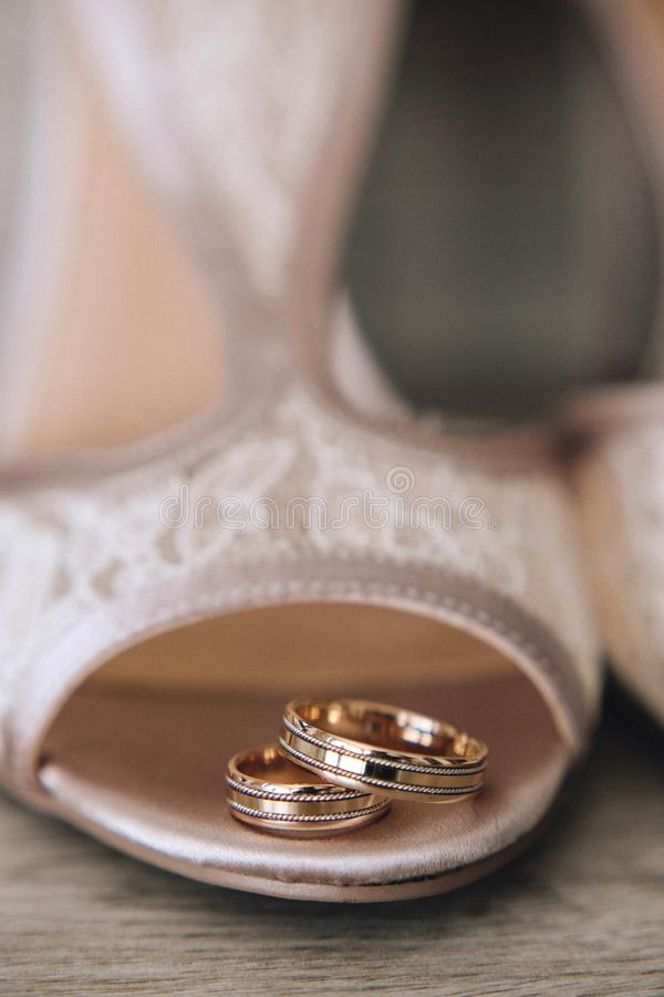 Gold wedding rings with a design are on the bride`s shoes with a lace. Close up. Vertical stock image