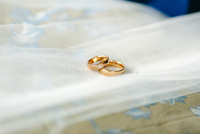 Gold wedding rings with a diamond on the background of the white bridal veil. royalty free stock photography