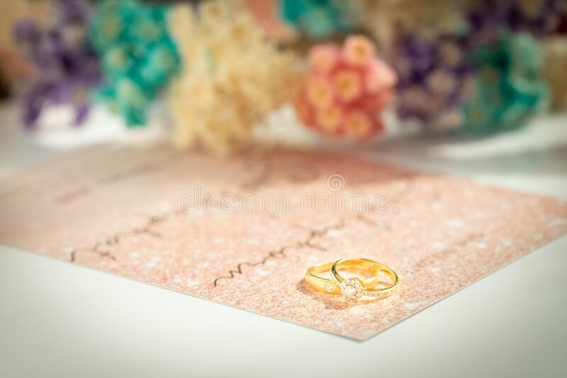 Gold wedding rings or engagement ring on Invitation Card background. Couple ring beautiful and elegant. Gift for marry or celebrat. E. Soft and selective focus royalty free stock photo