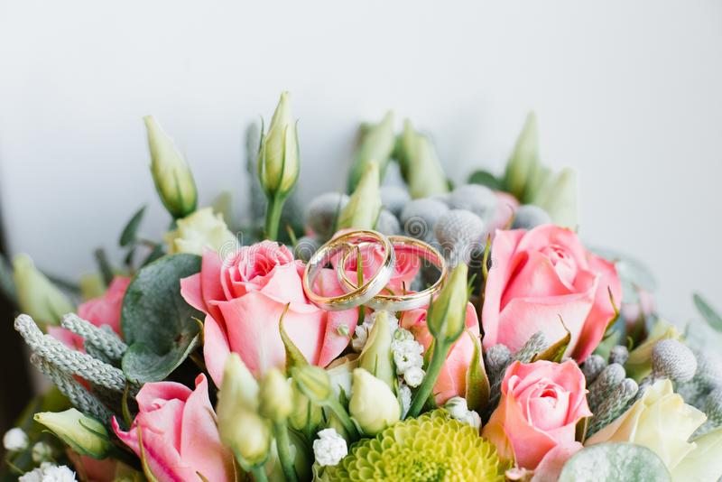 Gold wedding rings lie on the bride`s wedding bouquet of roses, eustoma, eucalyptus. Close up royalty free stock image